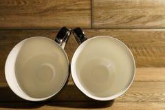Deux tasses de café vides sur le plancher en bois photos stock