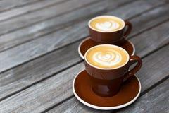 Deux tasses de cappuccino avec le coeur forment le latte-art sur le fond en bois Image stock