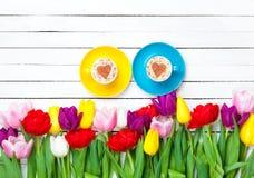 Deux tasses de cappuccino et de tulipes Photographie stock libre de droits