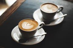 Deux tasses de cappuccino sur la table noire Photos libres de droits
