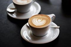Deux tasses de cappuccino sur la table noire Photographie stock libre de droits
