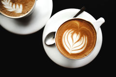 Deux tasses de cappuccino sur la table noire Photographie stock
