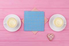 Deux tasses de cappuccino sur le fond rose Photographie stock libre de droits