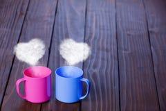 Deux tasses de couleur de café avec le coeur forment des vapeurs Photographie stock