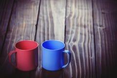 Deux tasses de couleur sur la table en bois Image stock