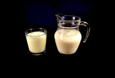 Deux tasses de lait sur le fond noir Image stock