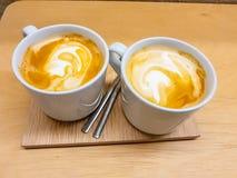 Deux tasses de latte avec ses formes de dessin de mousse Présenté sur un conseil en bois dans des tons chauds précieux photos libres de droits