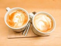 Deux tasses de latte avec ses formes de dessin de mousse Présenté sur un conseil en bois dans des tons chauds précieux photographie stock