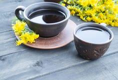 Deux tasses de support de thé sur de vieux conseils en bois avec des fleurs de camomille jaune image stock