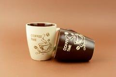 Deux tasses de temps de café se tenant et s'étendant sur le fond brun Photographie stock