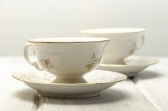 deux tasses de thé antiques sur le fond blanc Photo stock