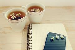 Deux tasses de thé avec des fleurs de ressort, un carnet et le téléphone portable Photographie stock libre de droits