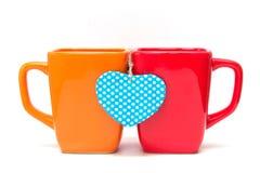 Deux tasses de thé avec la forme de coeur d'isolement sur le blanc. Photo stock