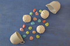 Deux tasses de thé avec les meringues colorées sur le fond bleu Photo stock