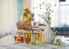 Deux tasses de thé de romum de camomille sur une table, avec les fleurs fraîches indoors photographie stock