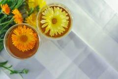 Deux tasses de thé de souci de calendula sur une table, avec les fleurs fraîches indoors images stock