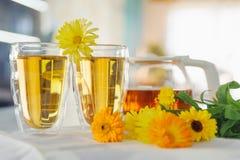 Deux tasses de thé de souci de calendula sur une table, avec les fleurs fraîches indoors photos stock