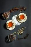 Deux tasses de thé sur le fond noir avec le thé de dispersion Image stock