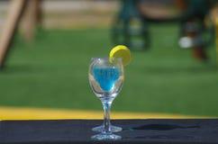 Deux tasses du Curaçao bleu boivent l'ensemble un midi de table photo libre de droits