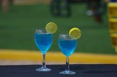 Deux tasses du Curaçao bleu boivent l'ensemble un midi de table images stock
