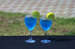 Deux tasses du Curaçao bleu boivent l'ensemble un midi de table photo stock