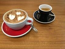 Deux tasses en céramique avec du café chaud boivent dans les plats rouges et noirs sur une table en bois Image libre de droits
