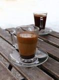 Deux tasses en verre de café turc, noir et avec du lait Image stock
