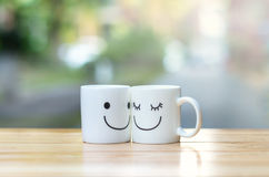 Deux tasses heureuses sur la table en bois avec le bokeh, au sujet du concept d'amour Photographie stock