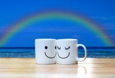 Deux tasses heureuses sur la table en bois sous la mer, le ciel et l'arc-en-ciel bleus Image stock