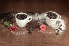 Deux tasses pleines des grains de café avec le bourgeon rouge se sont levées sur la table en bois Photographie stock libre de droits