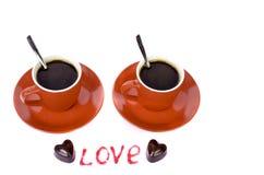 Deux tasses rouges, coeurs de chocolat et les mots Image libre de droits