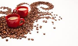 Deux tasses rouges d'expresso avec des grains de café Images stock