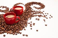 Deux tasses rouges d'expresso avec des grains de café Photos stock
