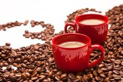 Deux tasses rouges d'expresso avec des grains de café Photos libres de droits