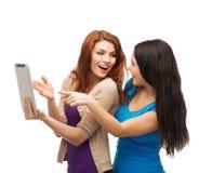 Deux teenages de sourire avec l'ordinateur de PC de comprimé Image libre de droits