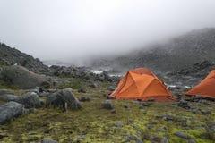 Deux tentes oranges le matin brumeux en montagnes images stock