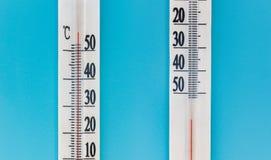 Deux thermomètres sur un fond bleu Très chaud ou froid Concept minimal image libre de droits