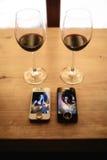 Deux téléphones, anneaux et deux verres de vin sur une table Image stock