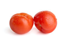 Deux tomates d'isolement avec les baisses + le chemin de découpage photos stock