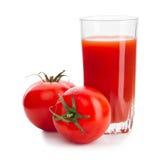 Deux tomates rouges avec le verre de jus de tomates Photographie stock