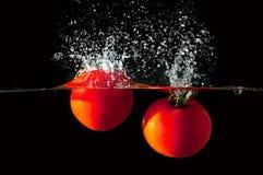 Deux tomates tombant dans l'eau Photographie stock