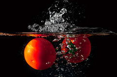 Deux tomates tombant dans l'eau Image stock
