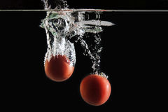Deux tomates tombant dans l'eau Images stock