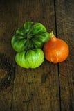 Deux tomates vertes de boeuf et une ceinture rouge de kuri sur une table en bois foncée photographie stock libre de droits