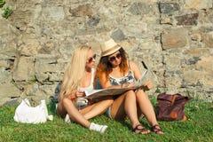 Deux touristes attirants de femme voyageant en vacances dans la ville Filles avec la carte de ville à la recherche des attraction Images libres de droits