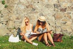Deux touristes attirants de femme voyageant en vacances dans la ville Filles avec la carte de ville à la recherche des attraction Photographie stock libre de droits
