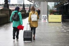 Deux touristes avec des valises marchent le long du remblai à la banque du sud de la Tamise On a un manteau vert, l'autre a un ye Photo stock