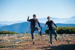 Deux touristes ayant l'amusement en haut de la montagne Photos libres de droits