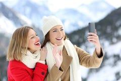 Deux touristes ayant un appel visuel en quelques vacances d'hiver Photographie stock