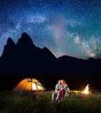 Deux touristes d'amants s'asseyant ensemble près du feu de camp et de la tente brillante la nuit sous des étoiles et regardant au Image stock